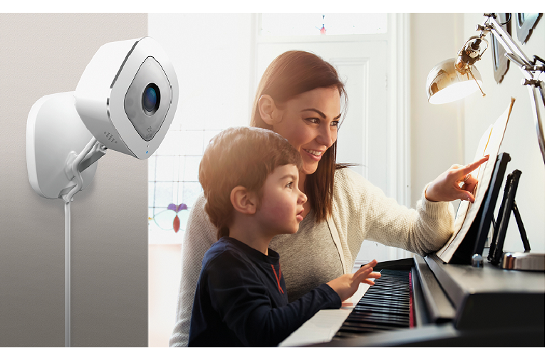 The Arlo Q Plus camera mounted on a wall, while a mother and son work on a computer in the background