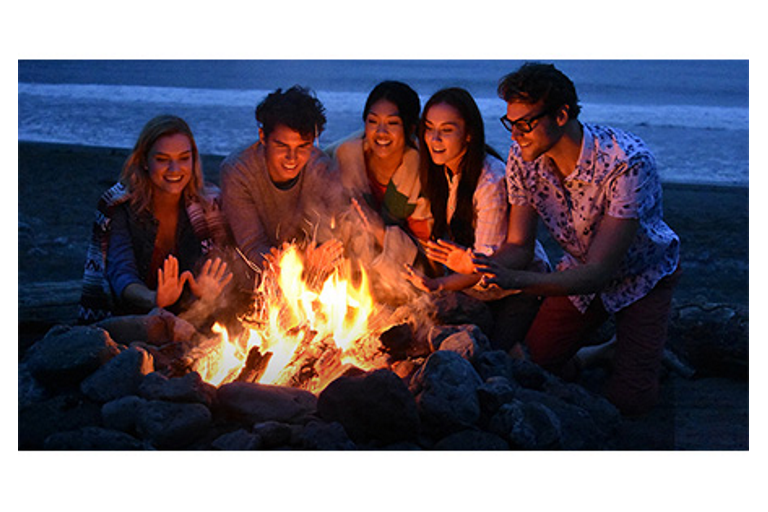 Some trendy folks around a fire