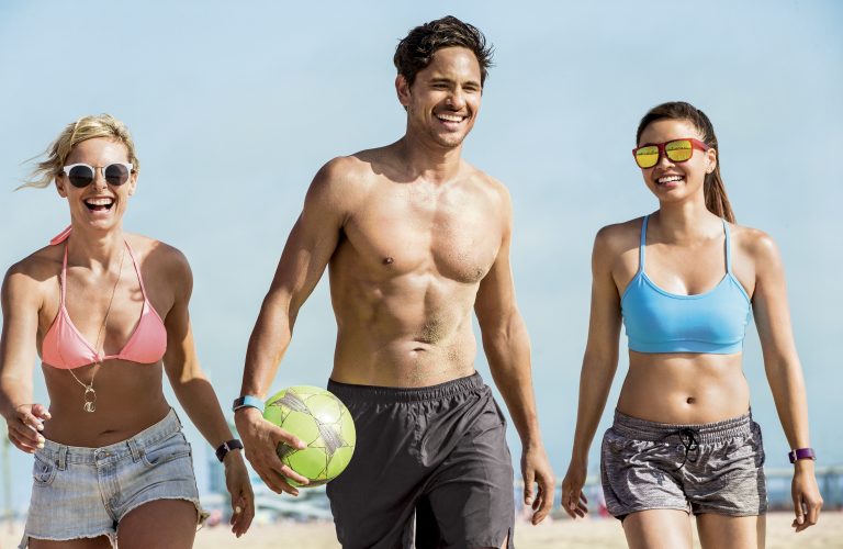 Friends on a beach together wearing Fitbit