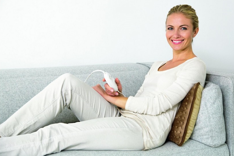 Woman on a couch using the Heatpad
