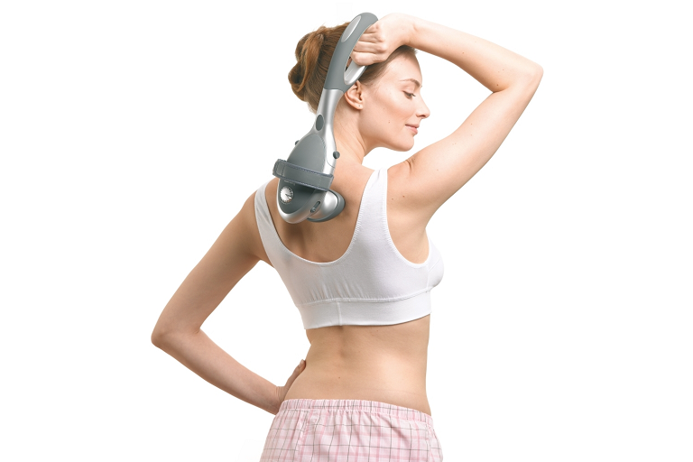 A woman using the Beurer massager on her back