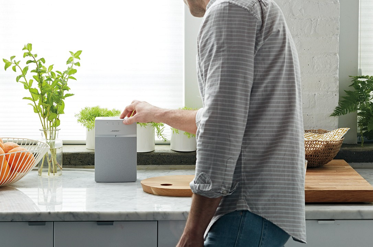 A man playing music from the Bose SoundTouch 10 on a kitchen bench
