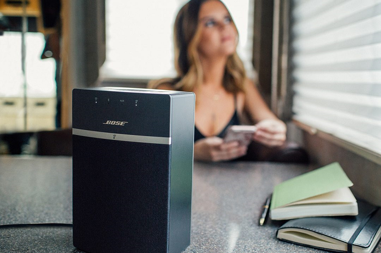 A woman playing music from her smart phone on the Bose speaker