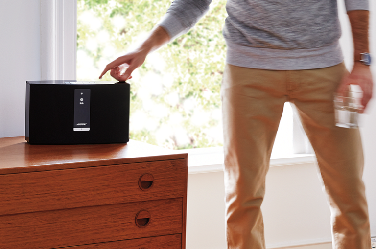 A man using the Bose SoundTouch 20 speaker on a living room sideboard