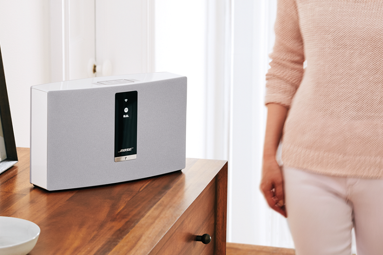 A woman walks by the Bose SoundTouch 20 Wireless Music System on a living room table