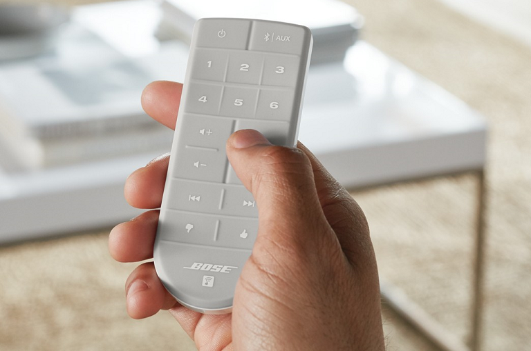 A man holding the SoundTouch 20 remote