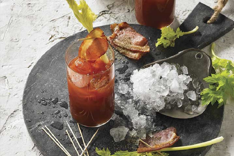 A smoked Bloody Mary cocktail on a serving tray with ice, bacon and celery