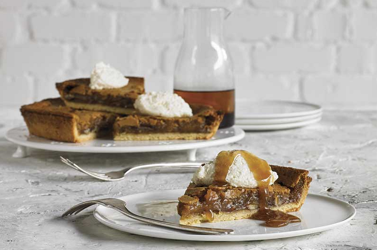 Slives of smoked caramel tart on plates with cream and caramel sauce