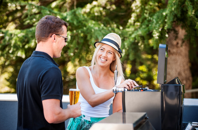 A man and woman beside a BBQ, pouring drinks from the BrewFlo keg