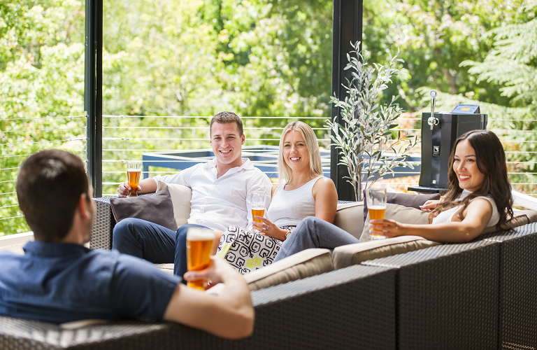 A group of friends share drinks from the BrewFlo in an outdoor space