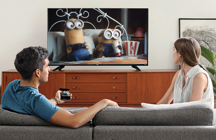 Two people watching a TV powered   by Chromecast.