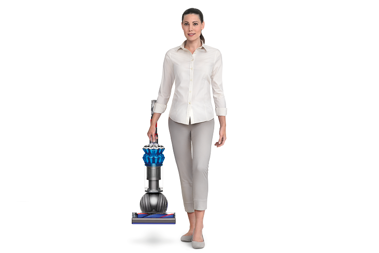 A woman carrying the Dyson Small Ball vacuum