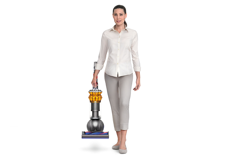 A woman carrying the Dyson Small Ball Multi Floor Vacuum