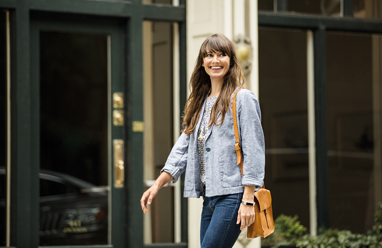 A woman wearing a Fitbit Alta and smiling brightly as she walks.