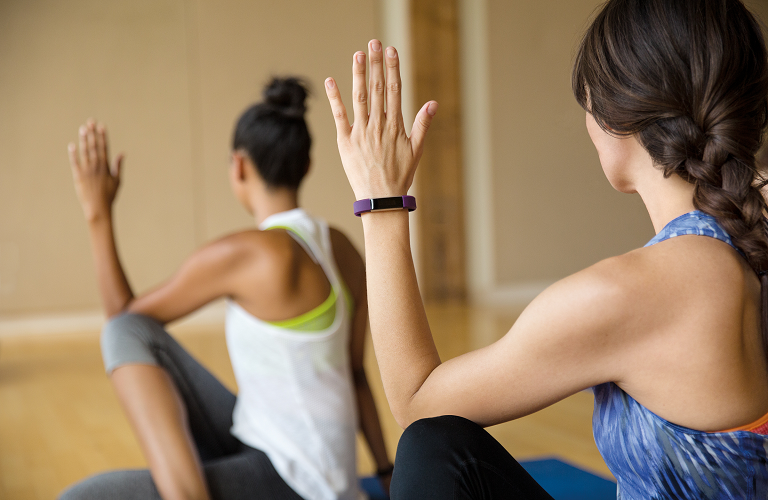 Two women wearing Fitbit Alta's during   exercising.