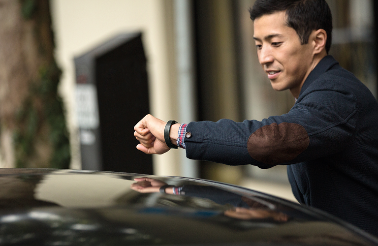 A man checking his Fitbit Alta as he gets into   his car.