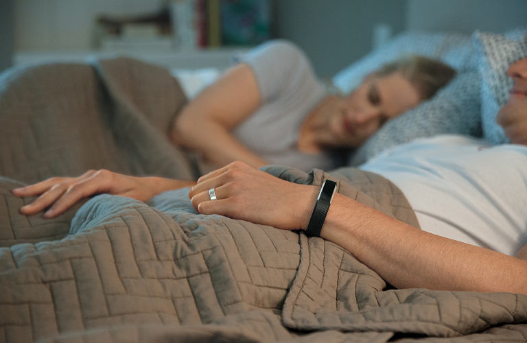 A couple asleep in bed and wearing a Fibit   Alta.