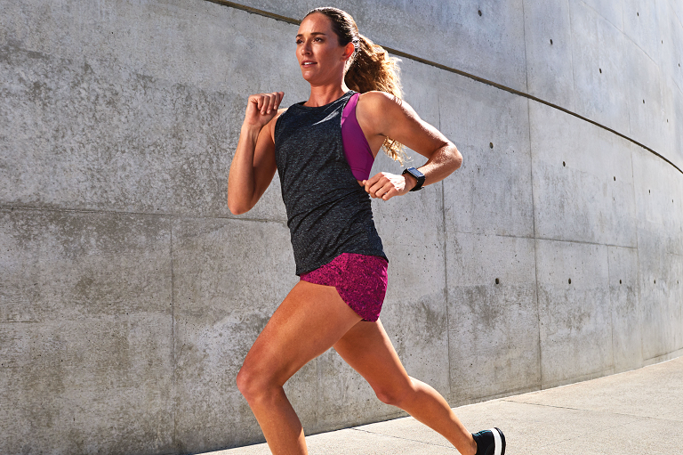 A woman running wearing the Garmin Vivoactive