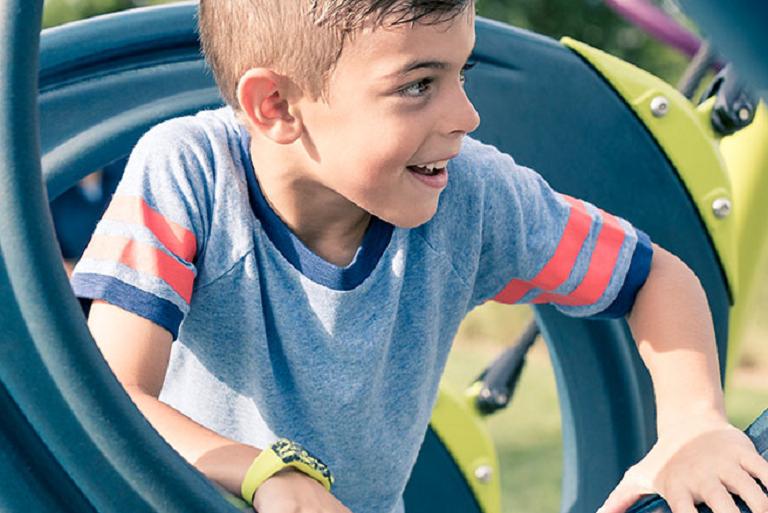 A boy climbing a play gym wearing the Vivofit Jr kids' activity tracker