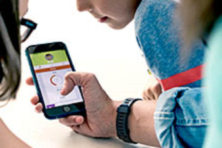 A parent using the Garmin Vivofit Jr app with kids watching