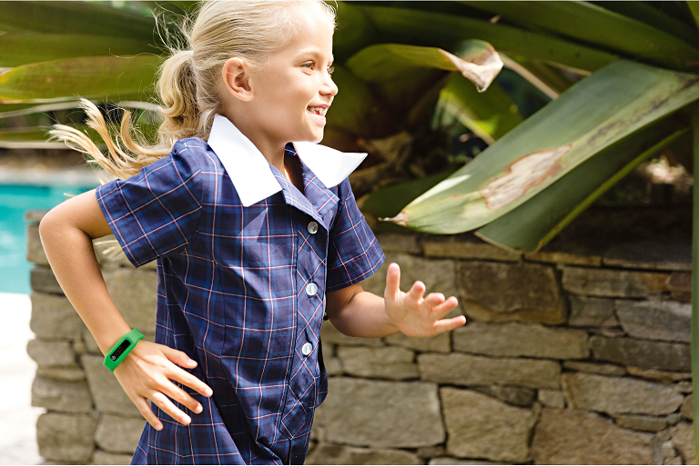 Girl running wearing the Milo activity tracker