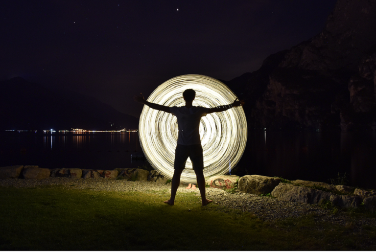 A nighttime photo of a man standing in front of a wheel of light