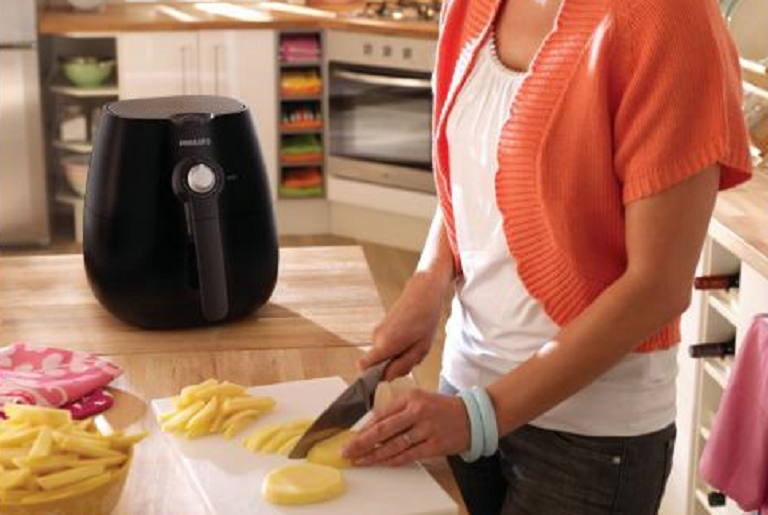 A woman cuts chips to cook in the Viva Collection Airfryer