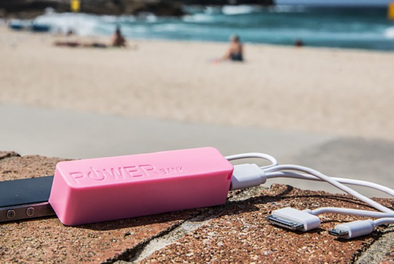 The Precision powerbank charging a phone at the beach