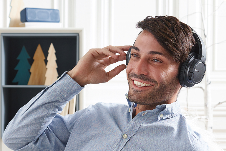 A man listening to music with the Sony portable speaker in the background