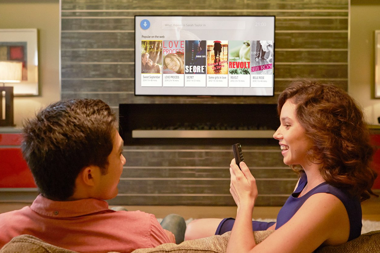 A couple sitting in front of the Sony TV using the voice search function