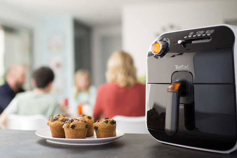 The DeLonghi Fry Delight with a family sharing a meal in the background