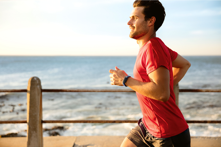 A man running on the beach wearing the TomTom fitness tracker