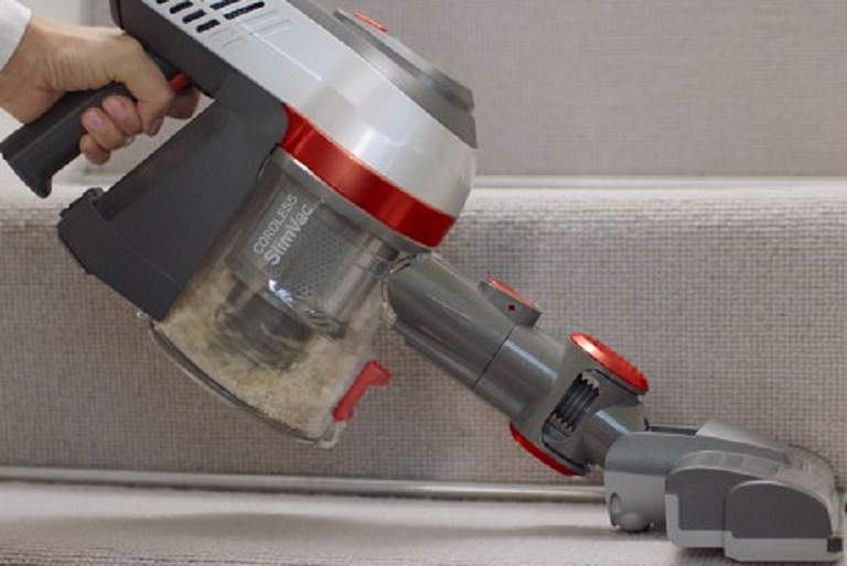 The handheld Vax vacuum cleaning carpeted stairs