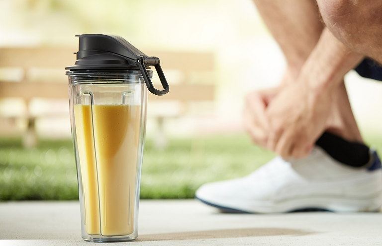 The Vitamix travel cup on a footpath, full of smoothie as a runner ties his shoes.