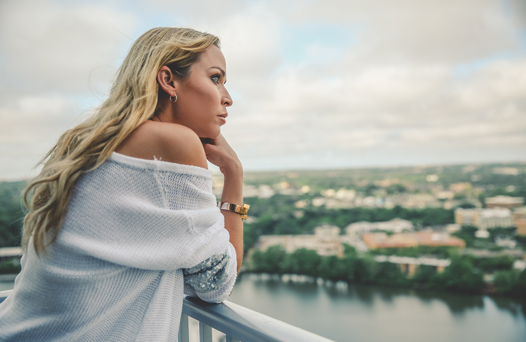 A woman standing on a balcony and 